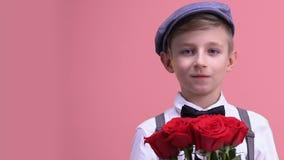 Χαριτωμένος κύριος με τη δέσμη των τριαντάφυλλων που εξετάζει τη κάμερα, που προετοιμάζεται για την ημερομηνία απόθεμα βίντεο