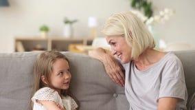 Χαριτωμένος λίγη εγγονή που μιλά στο grandma που έχει τη συνεδρίαση διασκέδασης στον καναπέ απόθεμα βίντεο