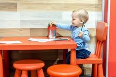 Χαριτωμένος λίγη καυκάσια ξανθή συνεδρίαση αγοριών μικρών παιδιών στον πίνακα και το σχέδιο στην περιοχή παιδιών στο λιανικό κατά στοκ φωτογραφία με δικαίωμα ελεύθερης χρήσης