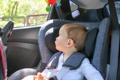 Χαριτωμένος λίγο αγοράκι στο κάθισμα ασφάλειας αυτοκινήτων που εξετάζει το παράθυρο Στοκ φωτογραφίες με δικαίωμα ελεύθερης χρήσης