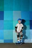 Χαριτωμένος λίγο αθλητικό αγόρι στον κύλινδρο που στέκεται ενάντια στον μπλε τοίχο γκράφιτι Στοκ Εικόνα