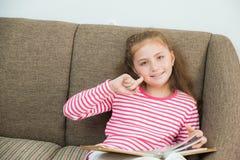 χαριτωμένος λίγο αμερικανικό κορίτσι παιδιών που διαβάζει ένα βιβλίο Στοκ Φωτογραφία