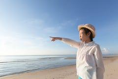 Χαριτωμένος λίγο ασιατικό καπέλο αχύρου ένδυσης κοριτσιών που περπατά στην παραλία με στοκ εικόνες