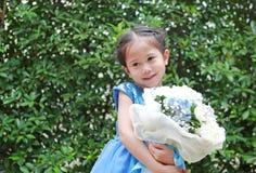 Χαριτωμένος λίγο ασιατικό κορίτσι παιδιών με την ανθοδέσμη των λουλουδιών στον κήπο στοκ φωτογραφία