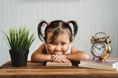 Χαριτωμένος λίγο ασιατικό μικρό παιδί μωρών που κάνει το αστείο πρόσωπο ή που χαμογελά διαβάζοντας τα βιβλία με το ξυπνητήρι στοκ φωτογραφία
