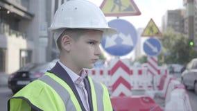 Χαριτωμένος λίγο επιτυχές αγόρι που φορούν το επιχειρησιακό κοστούμι και τον εξοπλισμό ασφάλειας και κράνος κατασκευαστών που στέ απόθεμα βίντεο