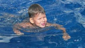 Χαριτωμένος λίγο ευρωπαϊκό αγόρι που παίζει και που επιπλέει στην πισίνα σε αργή κίνηση απόθεμα βίντεο
