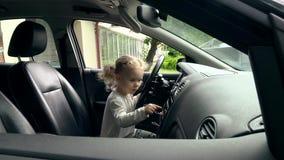 Χαριτωμένος λίγο κορίτσι οδηγών που εξερευνά το σαλόνι αυτοκινήτων Λατρευτό παιδικό παιχνίδι στο αυτοκίνητο απόθεμα βίντεο
