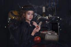 Χαριτωμένος λίγο κορίτσι παιδιών μαγισσών στο κοστούμι και τις διακοσμήσεις αποκριών Στοκ Εικόνες