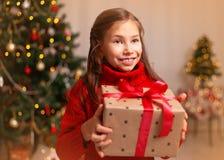 Χαριτωμένος λίγο κορίτσι παιδιών με το παρόν κιβώτιο δώρων κοντά στο χριστουγεννιάτικο δέντρο στο σπίτι στοκ εικόνα