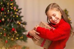 Χαριτωμένος λίγο κορίτσι παιδιών με το παρόν κιβώτιο δώρων κοντά στο χριστουγεννιάτικο δέντρο στο σπίτι στοκ εικόνες