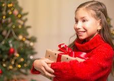 Χαριτωμένος λίγο κορίτσι παιδιών με το παρόν κιβώτιο δώρων κοντά στο χριστουγεννιάτικο δέντρο στο σπίτι στοκ εικόνα με δικαίωμα ελεύθερης χρήσης