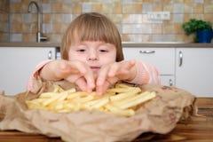Χαριτωμένος λίγο κοριτσάκι που απολαμβάνει τις τηγανιτές πατάτες στην κουζίνα στοκ φωτογραφίες με δικαίωμα ελεύθερης χρήσης