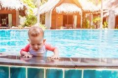 Χαριτωμένος λίγο μωρό που προσπαθεί να πάρει από τη λίμνη στοκ εικόνα