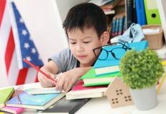 Χαριτωμένος λίγο παιδί που κάνει την εργασία που διαβάζει τις χρωματίζοντας σελίδες W βιβλίων Στοκ Φωτογραφία