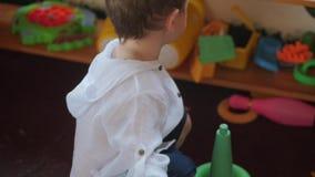 Χαριτωμένος λίγο παιδί που παίζει με τα παιχνίδια στο δωμάτιο παιχνιδιών Ευτυχής παιδική ηλικία έννοιας απόθεμα βίντεο