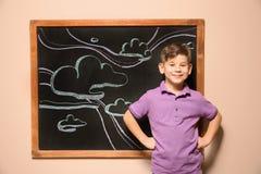 Χαριτωμένος λίγο παιδί που στέκεται στον πίνακα με συρμένο τον κιμωλία ουρανό στοκ φωτογραφία με δικαίωμα ελεύθερης χρήσης