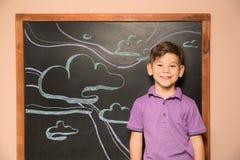 Χαριτωμένος λίγο παιδί που στέκεται στον πίνακα με συρμένο τον κιμωλία ουρανό στοκ εικόνες