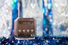 Χαριτωμένος λίγο σύγχρονο ραδιόφωνο με την κεραία σε ένα μπλε λαμπιρίζοντας υπόβαθρο Στοκ Φωτογραφία