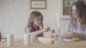 Χαριτωμένος λίγο χαμογελώντας κορίτσι που χρωματίζει τα ανατολικά αυγά με μια μικρή συνεδρίαση βουρτσών στον πίνακα με το mom της φιλμ μικρού μήκους