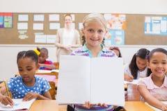 Χαριτωμένος μαθητής που χαμογελά στη κάμερα κατά τη διάρκεια της παρουσίασης κατηγορίας Στοκ Εικόνες