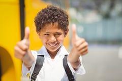 Χαριτωμένος μαθητής που χαμογελά στη κάμερα με το σχολικό λεωφορείο Στοκ φωτογραφία με δικαίωμα ελεύθερης χρήσης