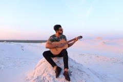 Χαριτωμένος νέος αρσενικός Άραβας απολαμβάνει τον ήχο της κιθάρας, καθμένος στο λόφο μέσα Στοκ Εικόνα