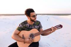 Χαριτωμένος νέος αρσενικός Άραβας απολαμβάνει τον ήχο της κιθάρας, καθμένος στο λόφο μέσα Στοκ Φωτογραφίες