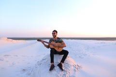Χαριτωμένος νέος αρσενικός Άραβας απολαμβάνει τον ήχο της κιθάρας, καθμένος στο λόφο μέσα Στοκ φωτογραφία με δικαίωμα ελεύθερης χρήσης