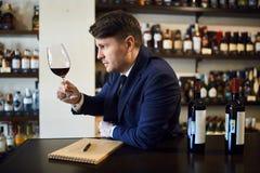 Χαριτωμένος νεαρός άνδρας στην καθιερώνουσα τη μόδα μπλε συνεδρίαση κοστουμιών στον πίνακα και τη δοκιμή του ποτού στοκ εικόνα με δικαίωμα ελεύθερης χρήσης