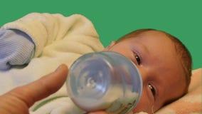 Χαριτωμένος ντυμένος νεογέννητος παρουσιάζει ότι πάρτε τα τρόφιμα από το κλειδί χρώματος μπουκαλιών φιλμ μικρού μήκους