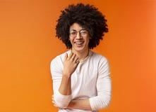 Χαριτωμένος ξένοιαστος μαύρος σγουρός τύπος που γελά στο πορτοκαλί υπόβαθρο στοκ εικόνες
