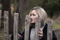 Χαριτωμένος ξανθός έφηβος με τους συμπαθητικούς αριθμούς που στέκονται πίσω από τον ξύλινο φράκτη Στοκ Εικόνα