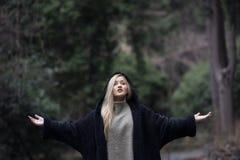 Χαριτωμένος ξανθός έφηβος στο δασικό λαιμό πόλο ένδυσης και το με κουκούλα σακάκι των γυναικών Στοκ Φωτογραφία