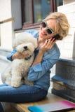 Χαριτωμένος ξανθός με το άσπρο σκυλί Bichon Frise Στοκ Φωτογραφίες