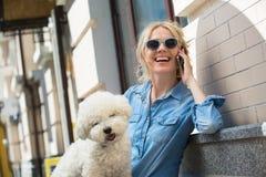 Χαριτωμένος ξανθός με το άσπρο σκυλί Bichon Frise Στοκ φωτογραφία με δικαίωμα ελεύθερης χρήσης