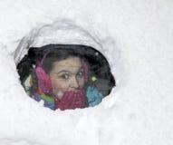 Χαριτωμένος οδηγός γυναικών έκπληκτος κοίταγμα από πίσω από ένα χιονώδες παράθυρο αυτοκινήτων Στοκ Φωτογραφίες