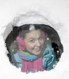 Χαριτωμένος οδηγός γυναικών που κοιτάζει από πίσω από ένα χιονώδες παράθυρο αυτοκινήτων Στοκ Εικόνες