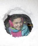 Χαριτωμένος οδηγός γυναικών που κοιτάζει από πίσω από ένα χιονώδες παράθυρο αυτοκινήτων Στοκ Φωτογραφία