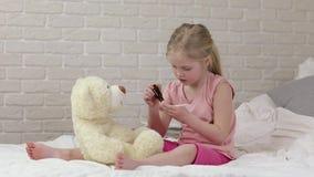 Χαριτωμένος παίζοντας γιατρός κοριτσιών παιδιών με τη teddy αρκούδα φιλμ μικρού μήκους