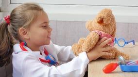 Χαριτωμένος παίζοντας γιατρός κοριτσιών παιδιών με τη teddy αρκούδα απόθεμα βίντεο