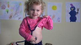 Χαριτωμένος παίζοντας γιατρός μικρών κοριτσιών στο σπίτι με το στηθοσκόπιο φιλμ μικρού μήκους
