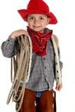 Χαριτωμένος πολύ νέος κάουμποϋ που κρατά ένα χαμόγελο σχοινιών στοκ φωτογραφίες