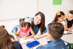 Χαριτωμένος προσχολικός δάσκαλος που βοηθά έναν σπουδαστή στοκ φωτογραφία με δικαίωμα ελεύθερης χρήσης
