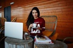 Χαριτωμένος σπουδαστής κοριτσιών που γράφει μια συνεδρίαση διάλεξης στο πεζούλι στοκ φωτογραφία