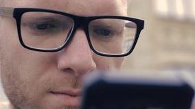Χαριτωμένος τύπος που βγάζει φύλλα μέσω της περιοχής σε ένα smartphone φιλμ μικρού μήκους