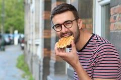 Χαριτωμένος τύπος που τρώει μια βάφλα στις Βρυξέλλες, Βέλγιο στοκ εικόνα