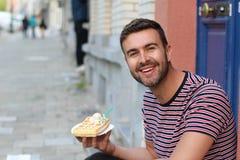 Χαριτωμένος τύπος που τρώει μια βάφλα στις Βρυξέλλες, Βέλγιο στοκ εικόνες