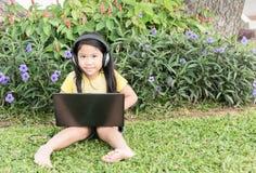 Χαριτωμένος υπολογιστής παιχνιδιού κοριτσιών με το ακουστικό στο πάρκο Στοκ Εικόνες