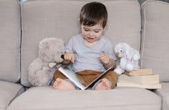 Χαριτωμένος χαμογελώντας λίγη συνεδρίαση βιβλίων ανάγνωσης αγοράκι στον καναπέ με το teddy παιχνίδι αρκούδων και το κουνέλι λαγου στοκ εικόνες